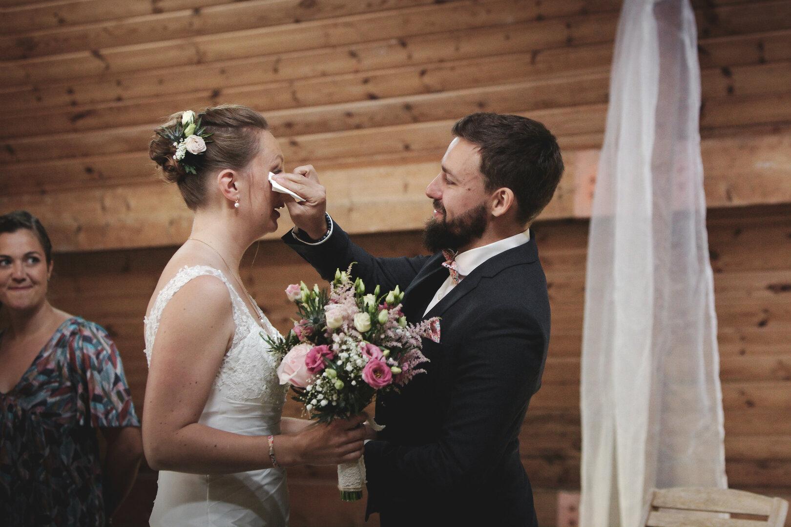 Le Marié essuie une larme de bonheur sur la joue de la mariée