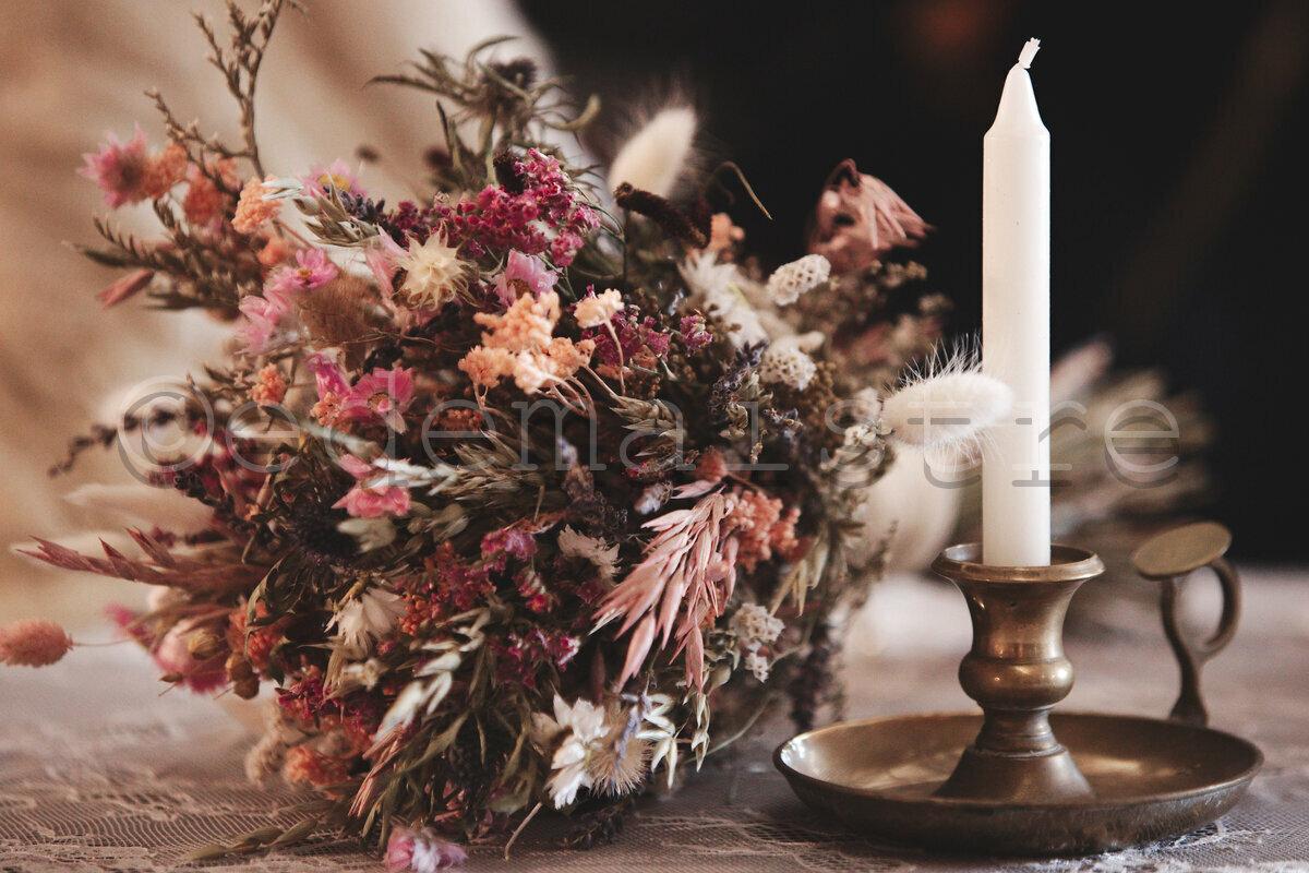 bouquet de la mariée posé à coté d'un bougeoir